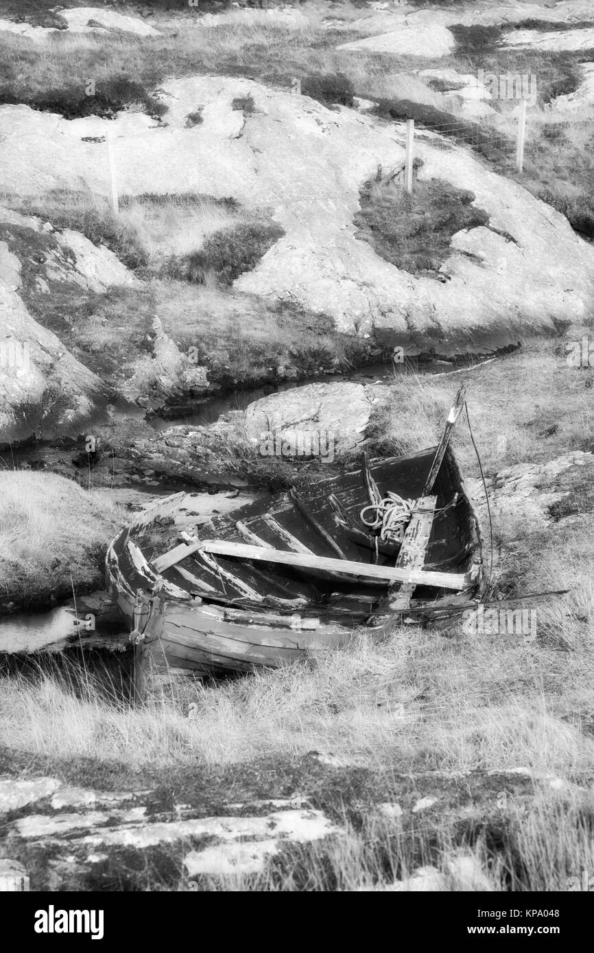 Abandoned rowing boat at Flodabay, Isle of Harris, Outer Hebrides. Monochrome image given an infrared treatment. - Stock Image