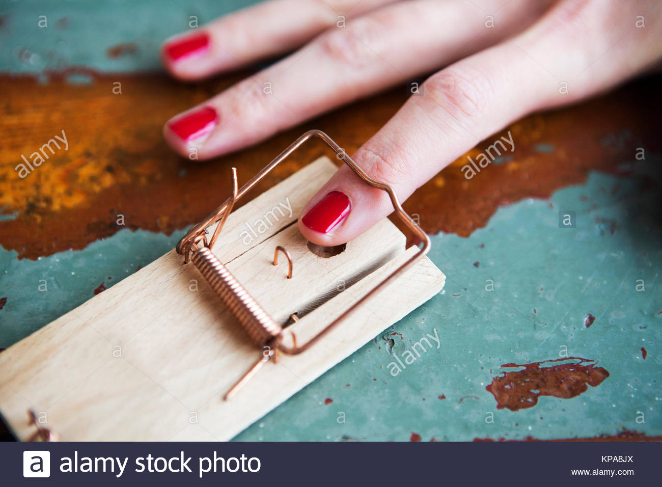 closeup of woman's finger in mousetrap - Stock Image