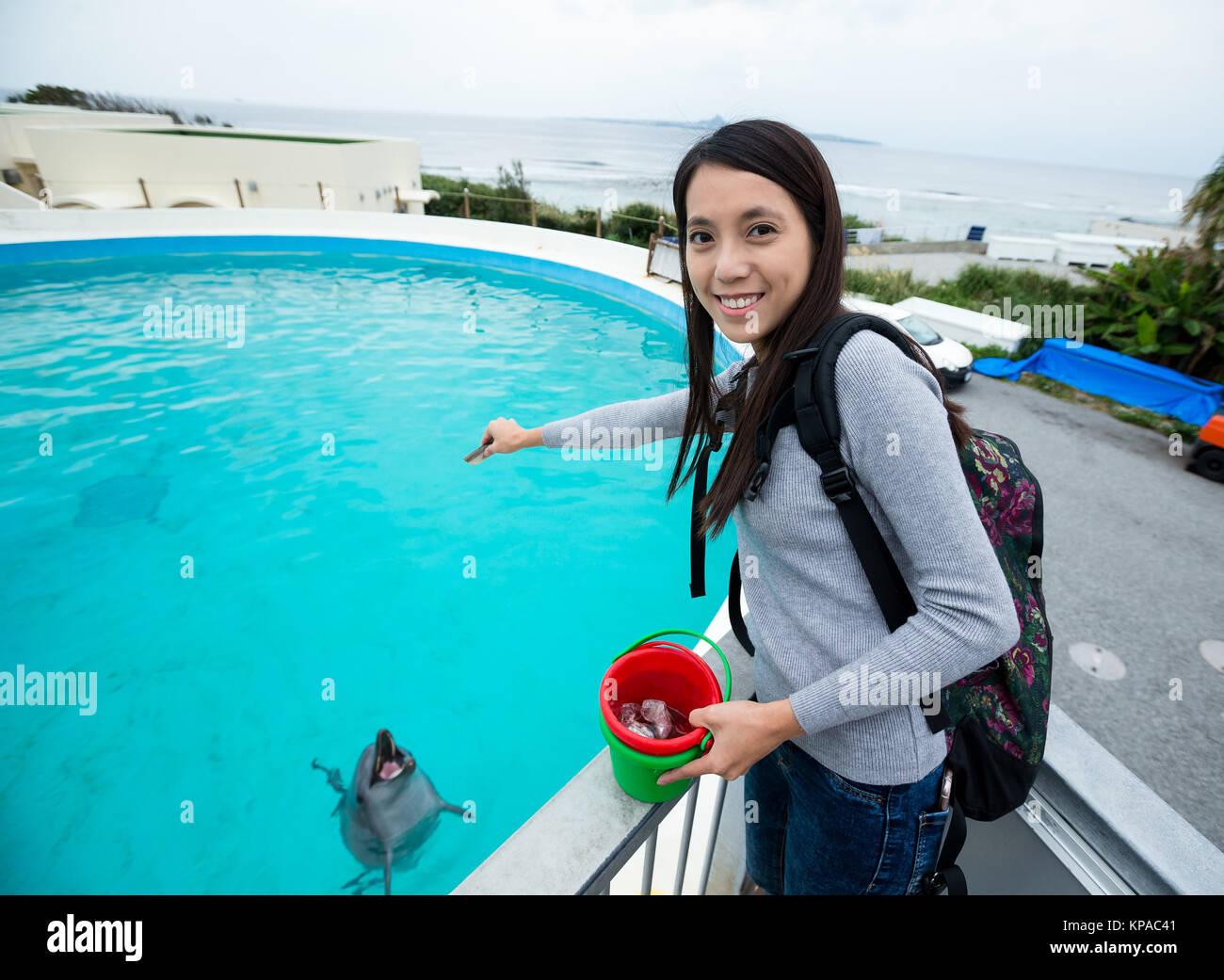 Young Woman feeding dolphin in aquarium - Stock Image