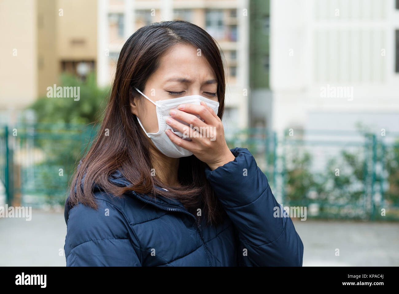 Young woman with face mask having cold - Stock Image