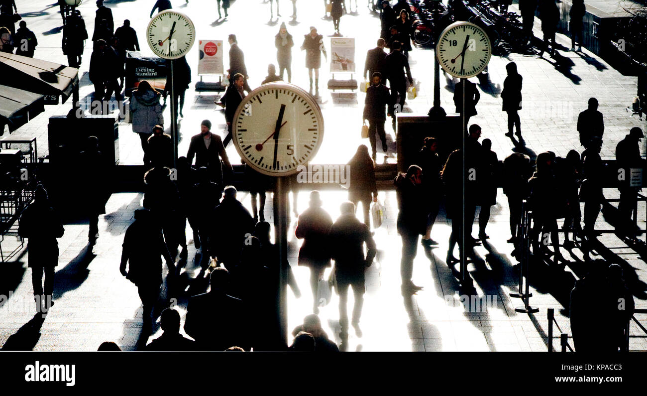 Pedestrians walk past decorative clocks in the Canary Wharf financial district in east London, Britain December - Stock Image