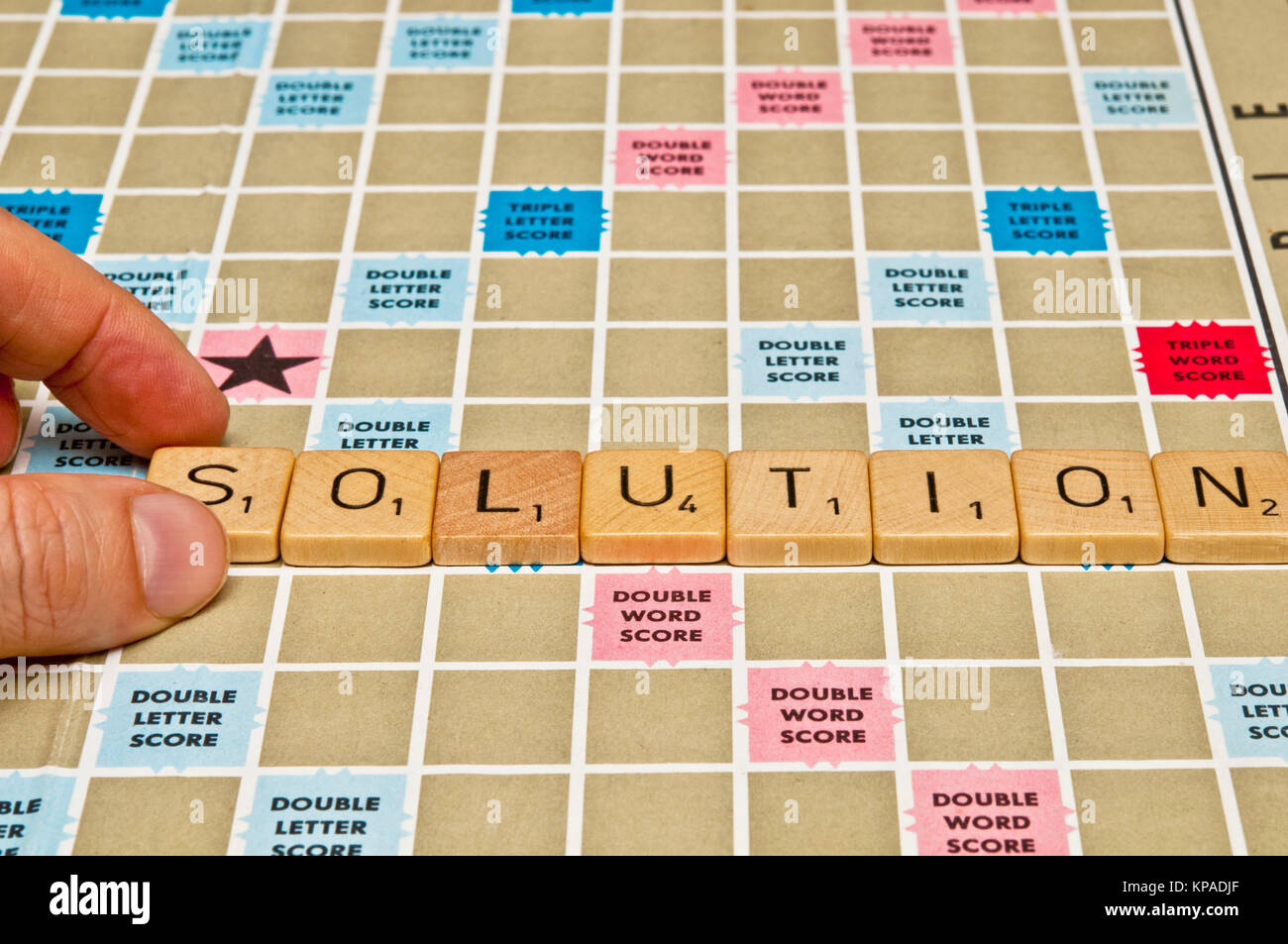 word solution spelled with scrabble tiles - Stock Image