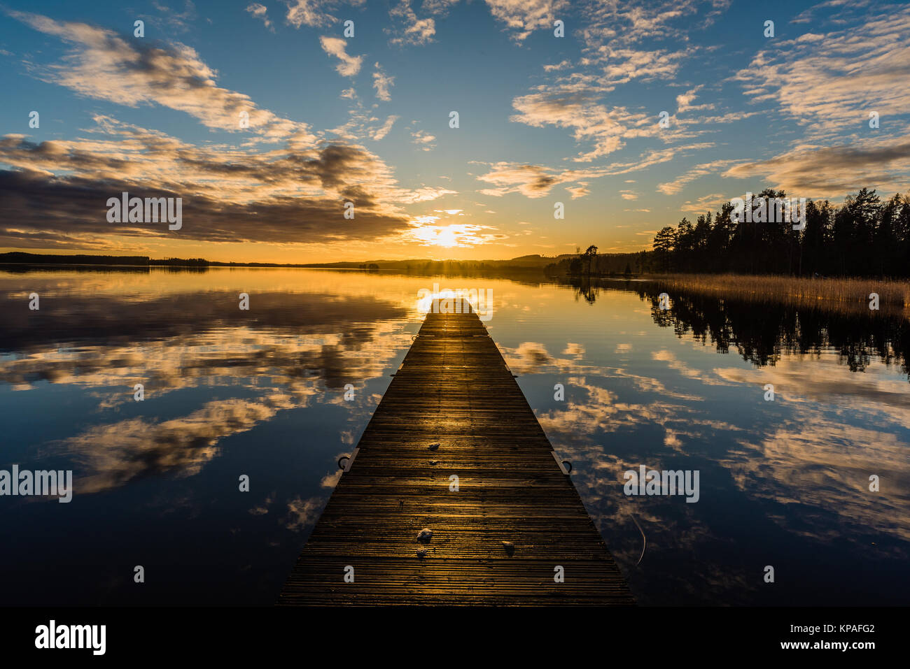 Sunset over a lake in Nykroppa, Filipstad, Sweden with a jetty - Stock Image