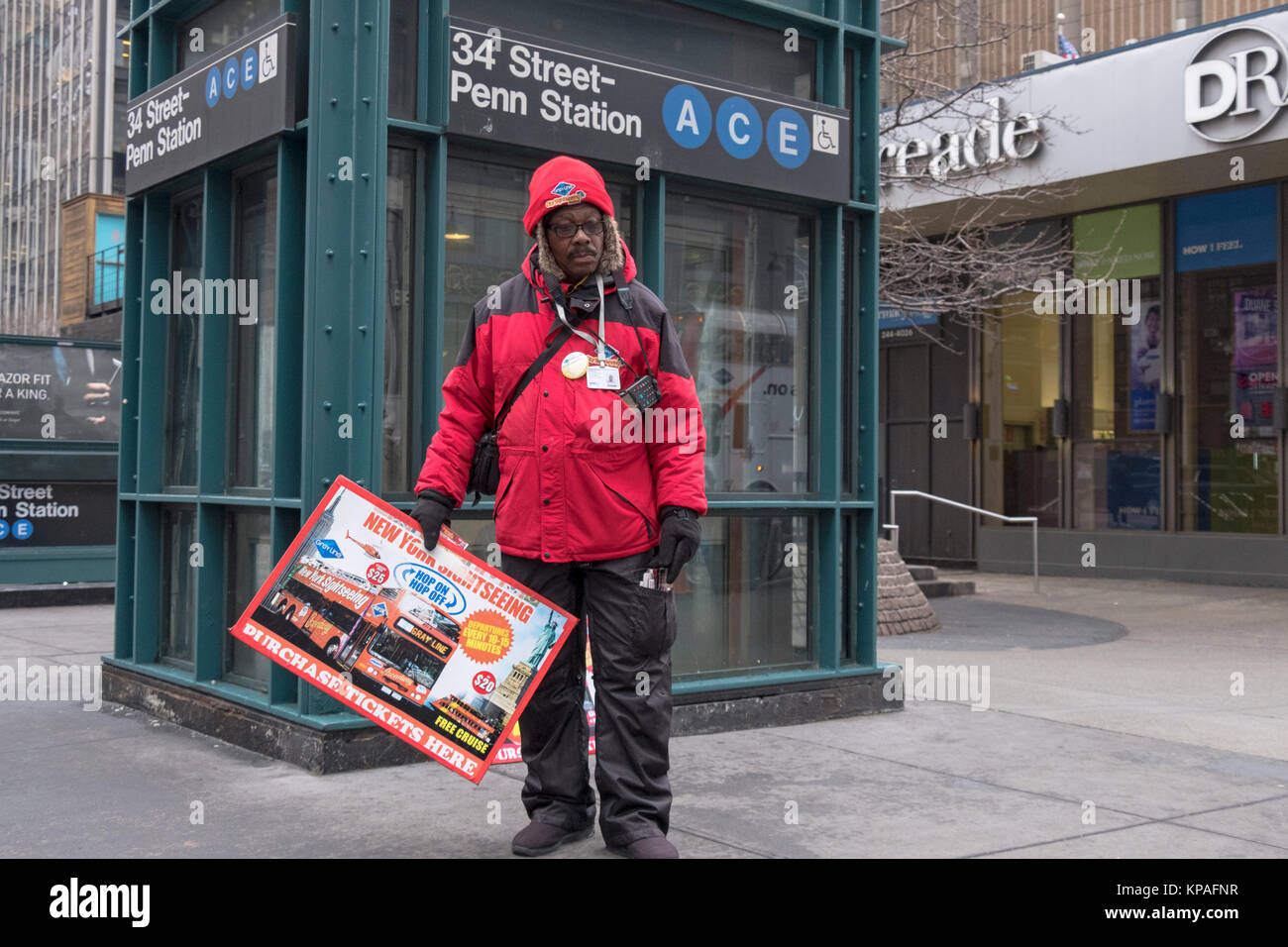A candid photo of a man who sells sightseeing bus tickets to tourists. In the Herald Square section of MIdtown Manhattan, - Stock Image