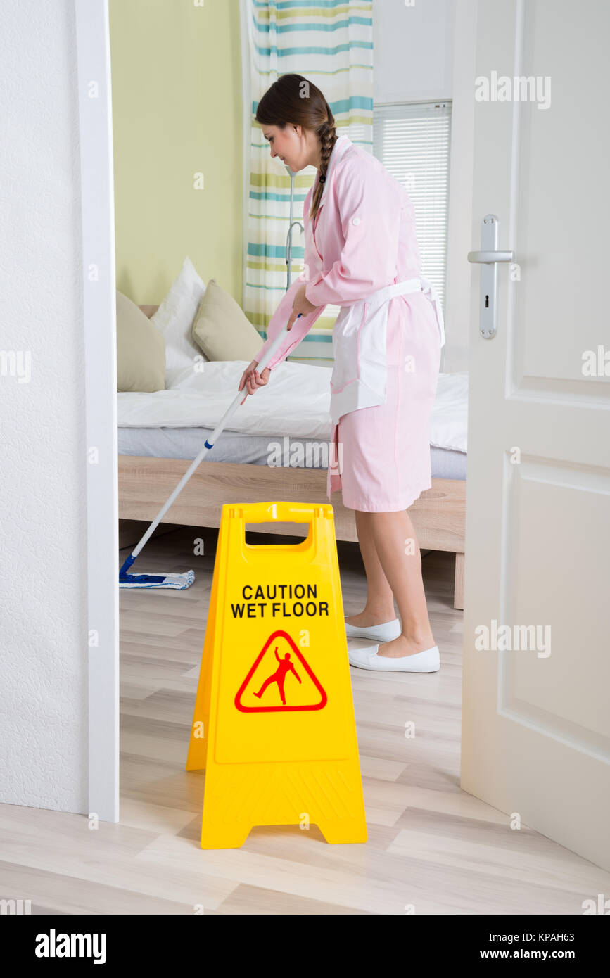 Female Housekeeper Cleaning Floor With Mop - Stock Image
