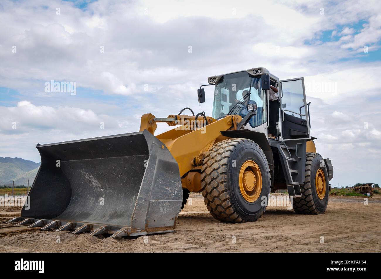 landscape photo of wheel loader in construction site with cloudy sky - Stock Image