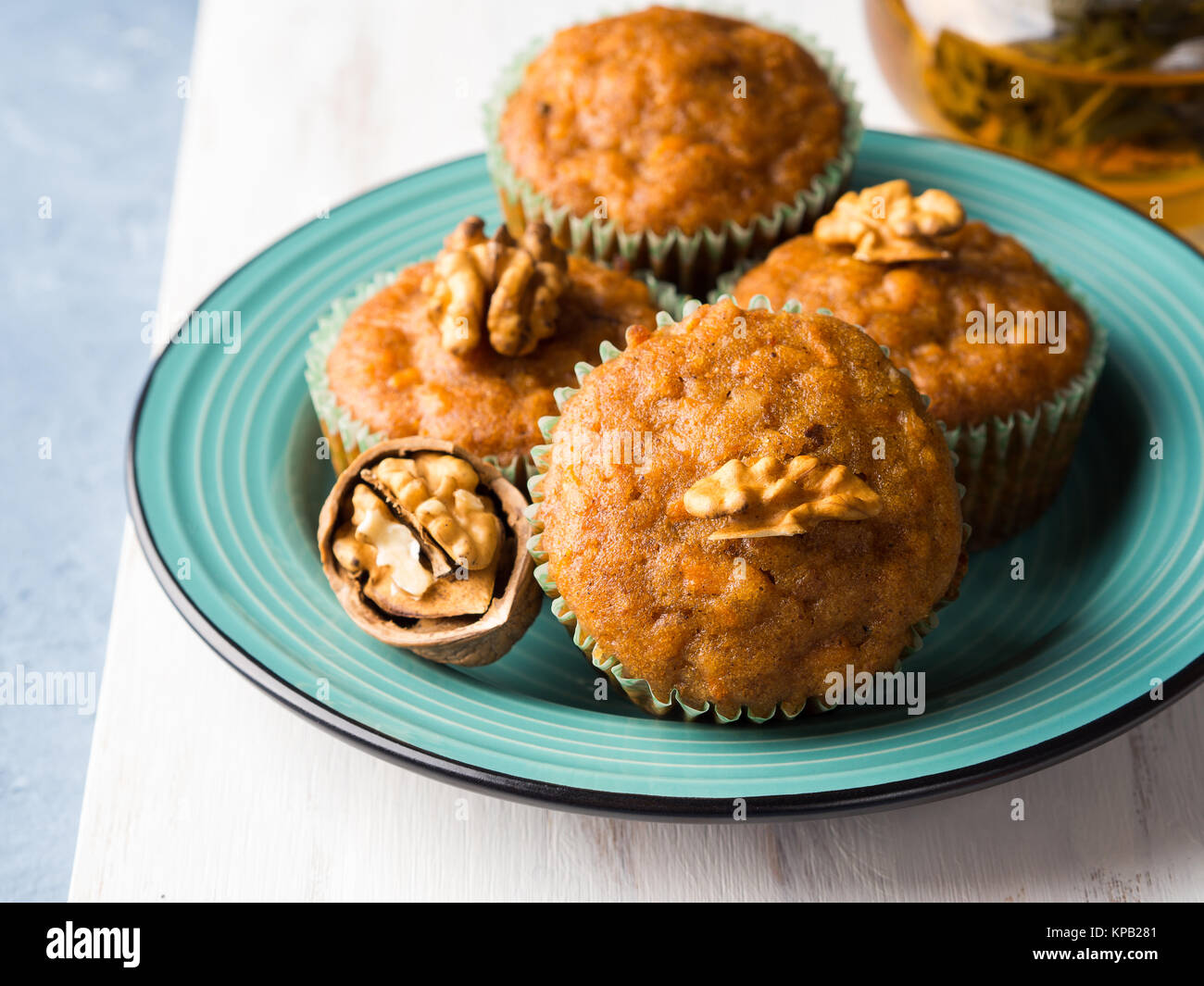 Home made Carrot spiced muffins with walnuts on green dish. - Stock Image