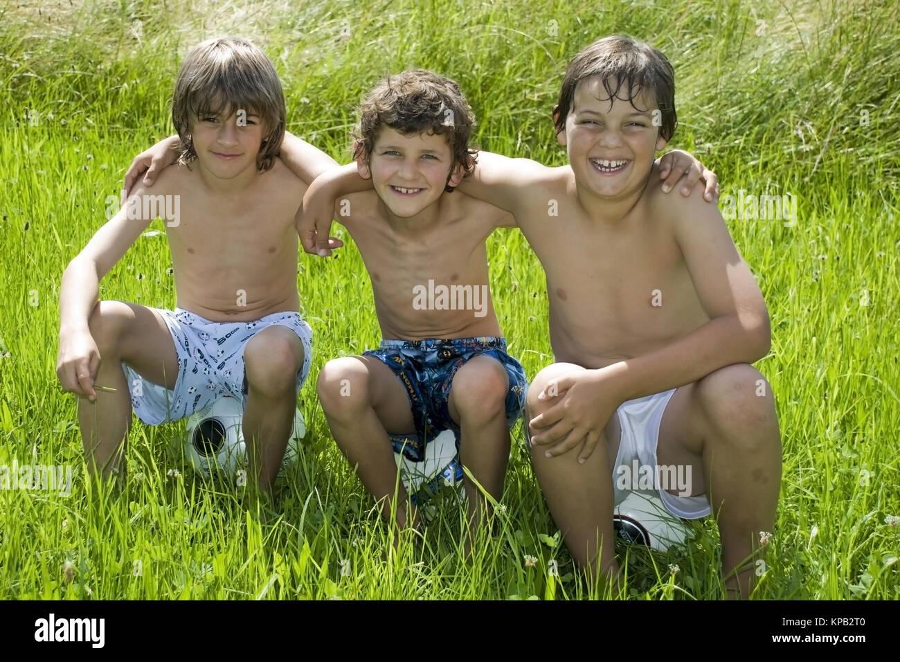 Model release, Drei Freunde in der Wiese - three boy friends - Stock Image