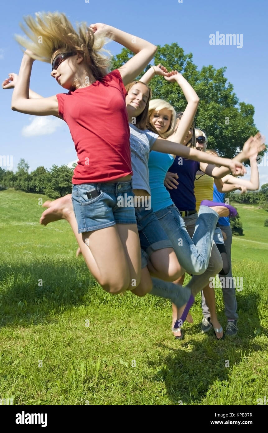 Model release, Jugendliche Maedchen springen in der Wiese - teenage girls jumping in meadow - Stock Image