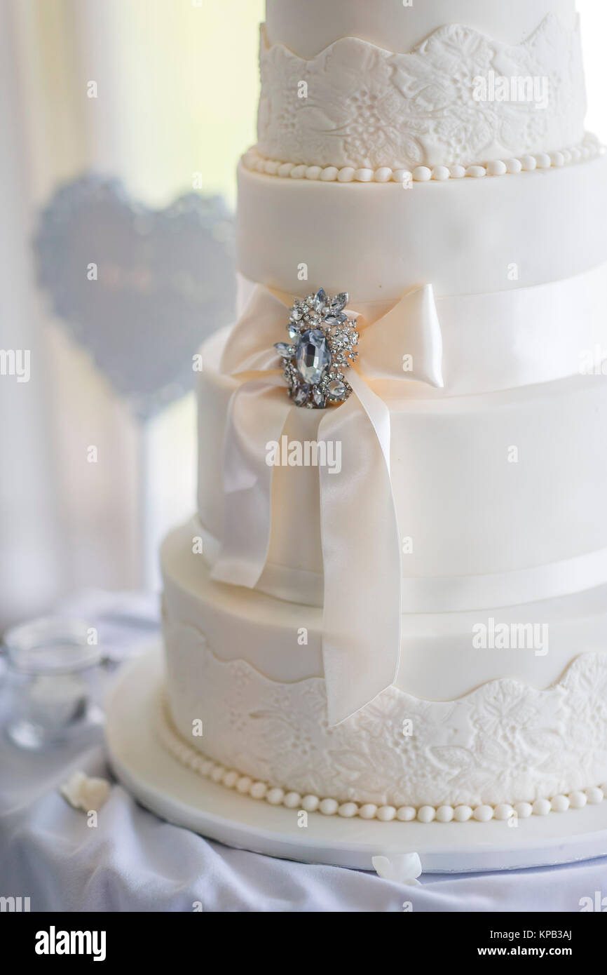 Wedding cake at a reception decortaed with flowers - Stock Image