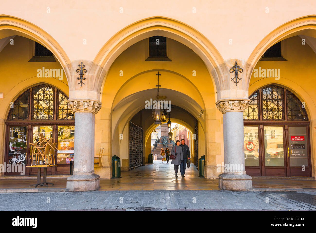 Cloth Hall Krakow, a middle aged couple walk under the arcade of the 16th Century Cloth Hall (Sukiennice) in the - Stock Image