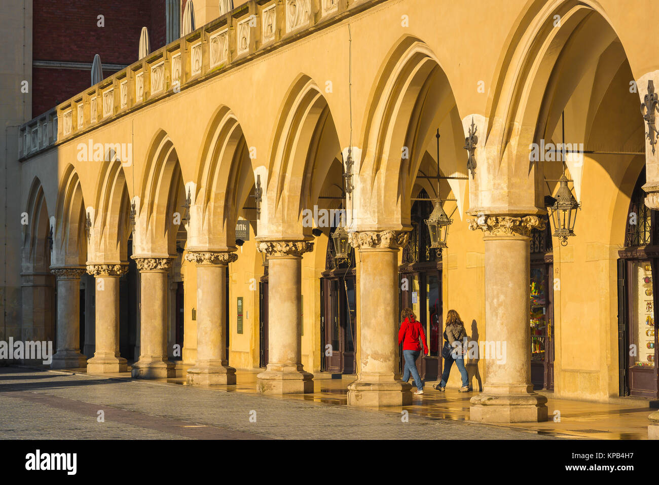 Colonnade arcade Europe, two young women walk through a colonnade of the Renaissance Cloth Hall (Sukiennice) in - Stock Image