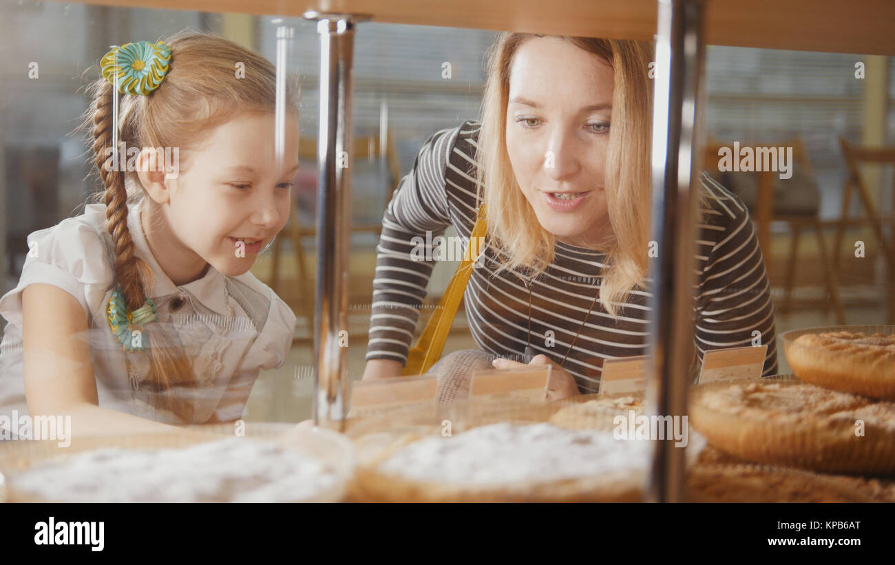 Girl with a pigtail and her mom look at the pies in the window choosing - Stock Image