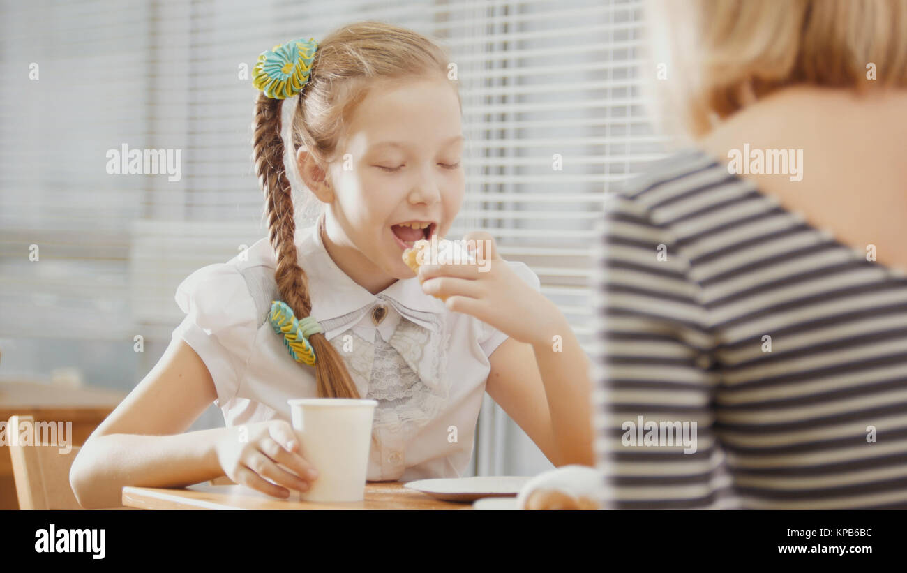 Girl with pigtails eats cakes with her mum in the cafe - Stock Image