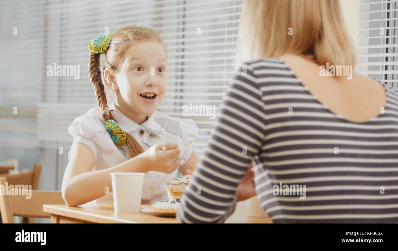 Girl with pigtail with her mum in the cafe - teen feels surprised - Stock Image