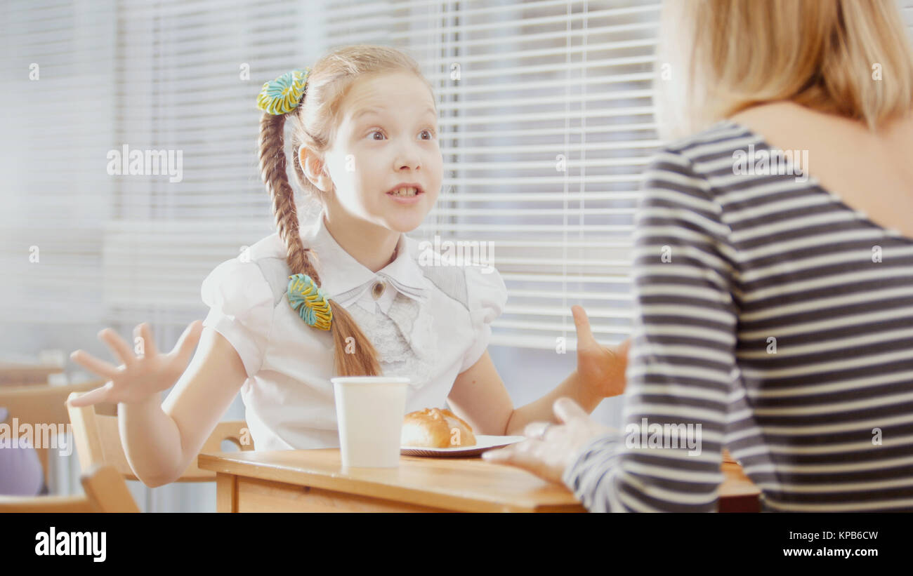 Girl with mommy in cafe - teen explains something for mother - Stock Image