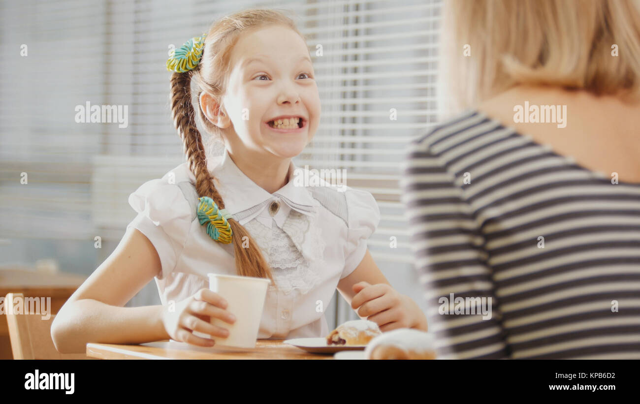 Daughter and mother are sitting in a cafe, eating sweetsand talking emotionally - Stock Image