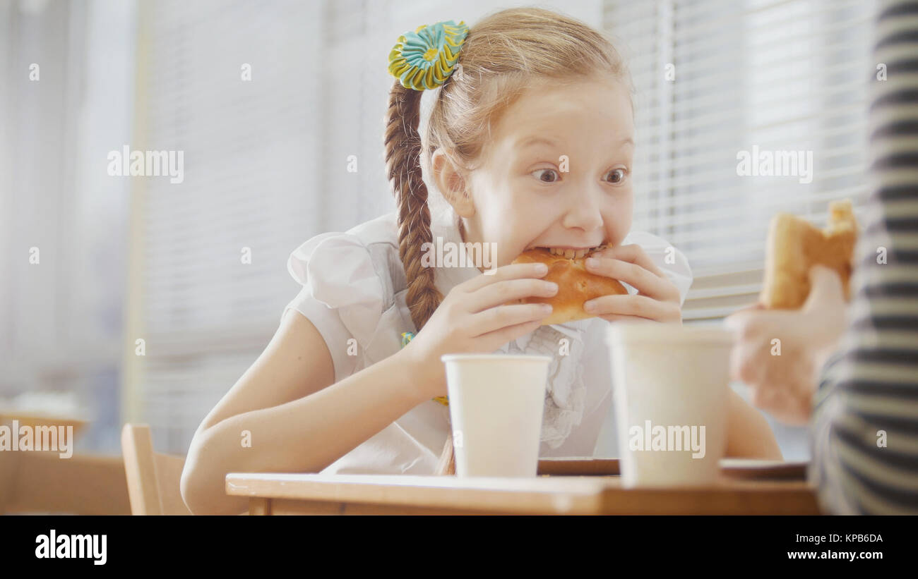 Girl with pigtail is eating sweets in the cafe - Stock Image