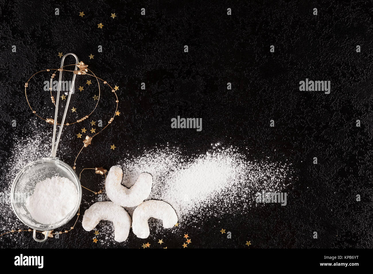 Sifter with spilled sugar with Christmas Cookies from above on dark surface. - Stock Image