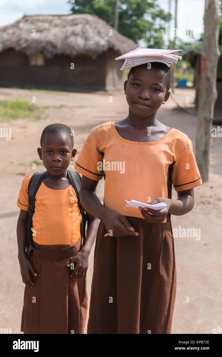 Two school girls on their way home, village near Mafi-Kumase Proper, Volta Region, Ghana, Africa - Stock Image