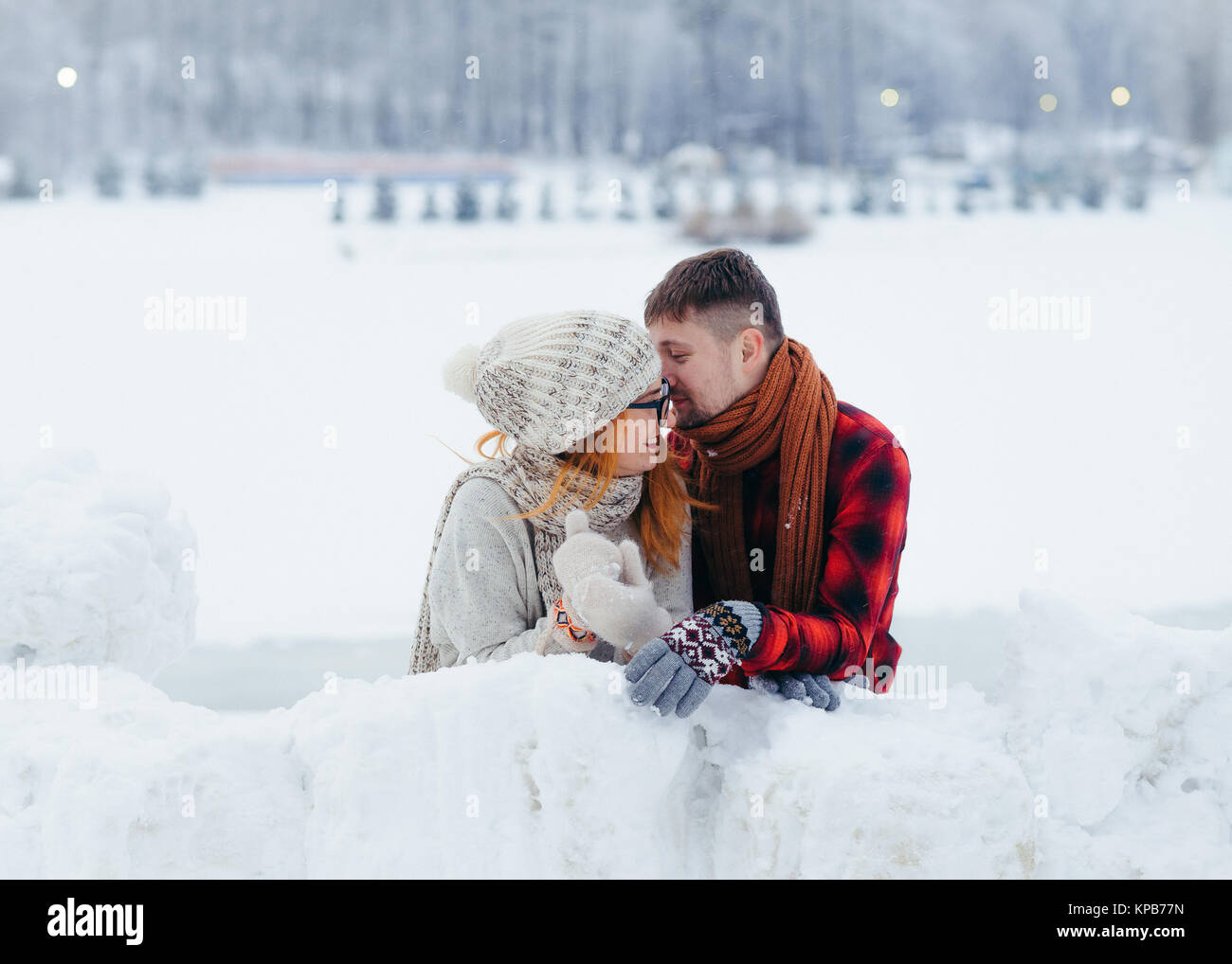 The handsome man is whispering something funny in the ear of his laughing girlfriend. Winter village location. Stock Photo