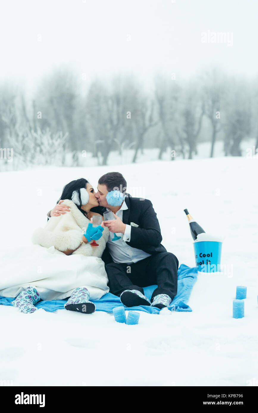 Vertical Happy Beautiful Newlyweds Kissing Picnic Winter Blue Colours Timespending Snowy Plaid. - Stock Image