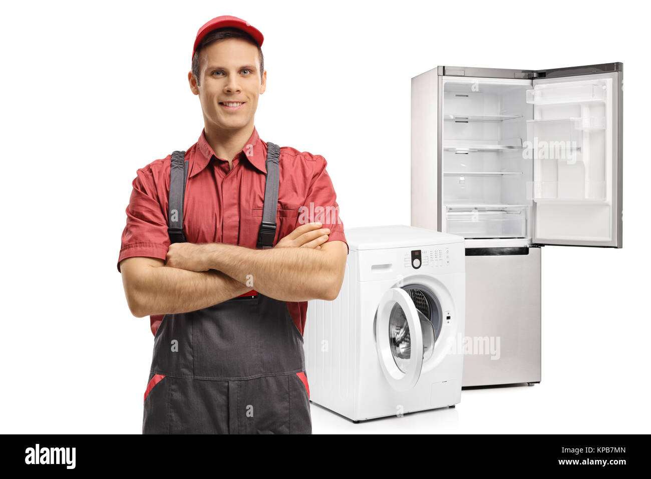 Repairman with his arms folded in front of a washing machine and a refrigerator isolated on white background - Stock Image