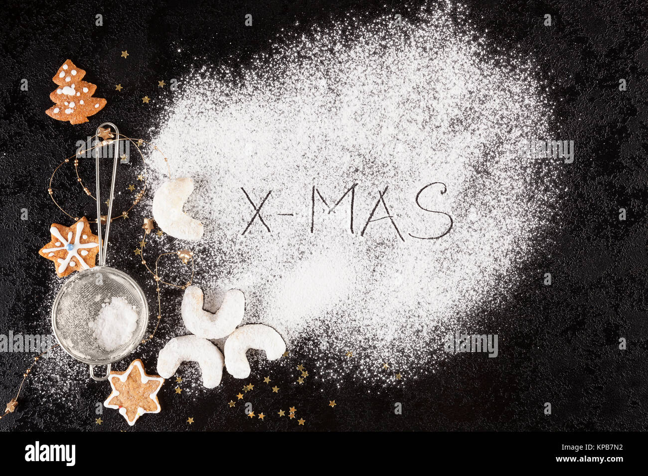 Xmas concept. Christmas cookies with sifter and spilled sugar from above. - Stock Image
