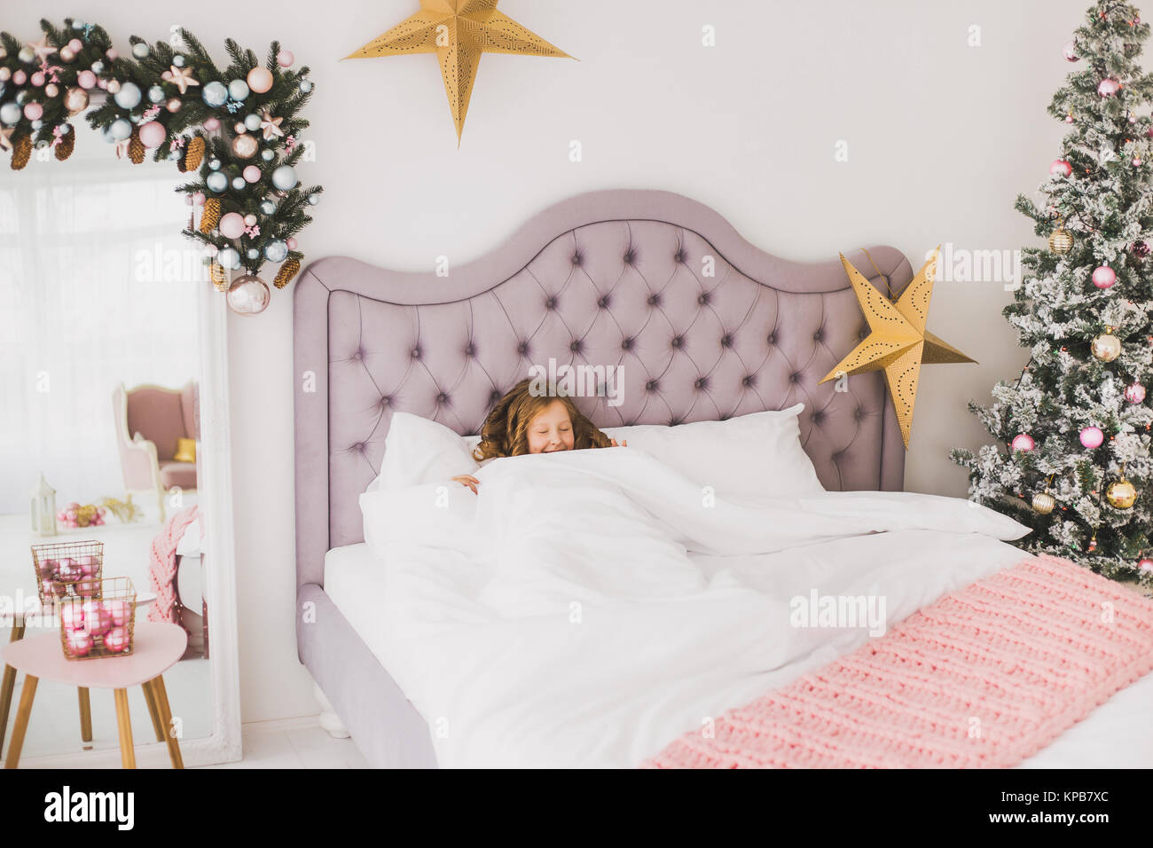 Portrait of cute funny little girl on Christmas morning in white home interior. Child pretending to be sleeping - Stock Image