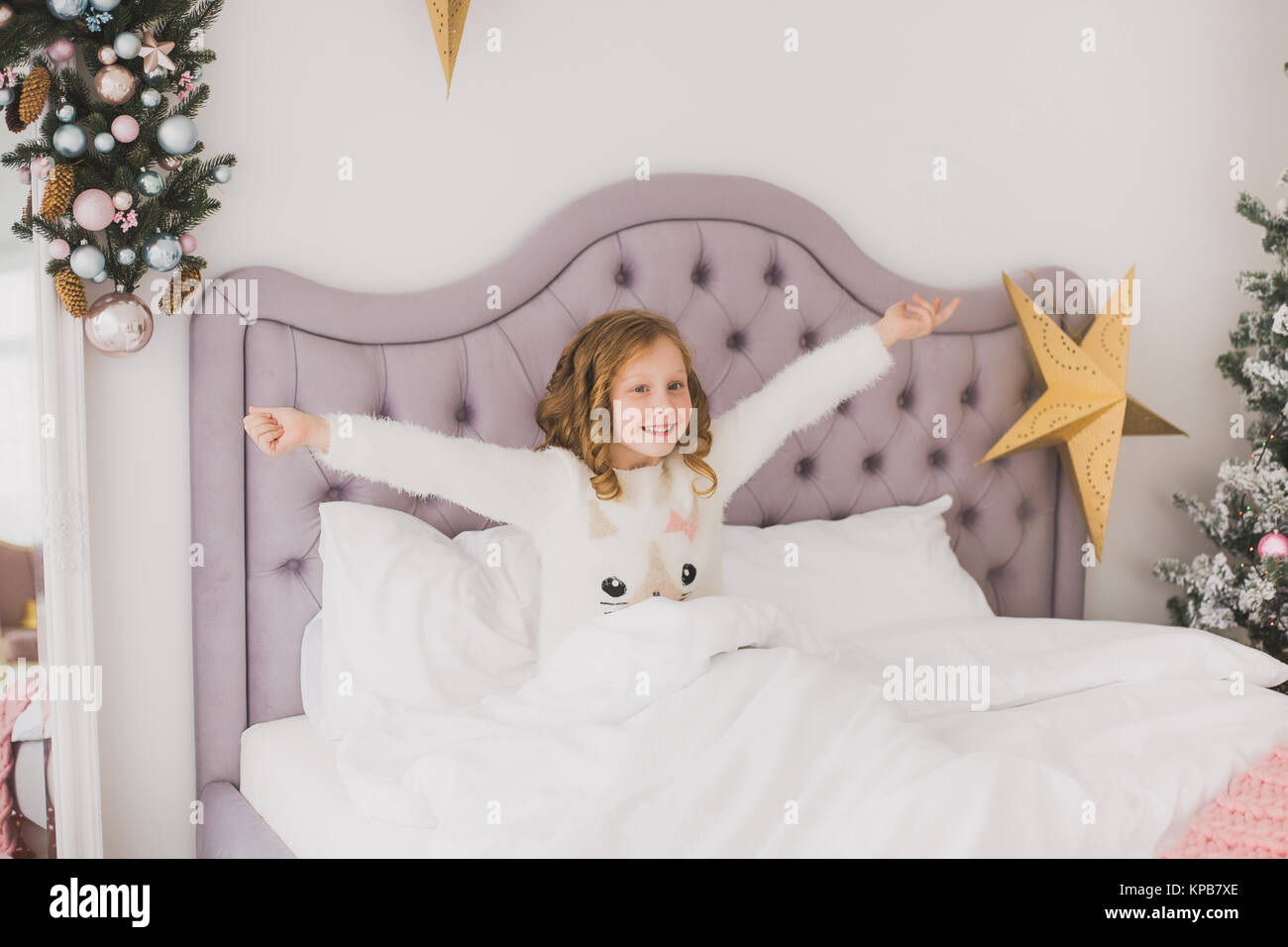 Portrait of cute funny little girl on Christmas morning in white home interior. Child cheerfully sitting in bed. - Stock Image