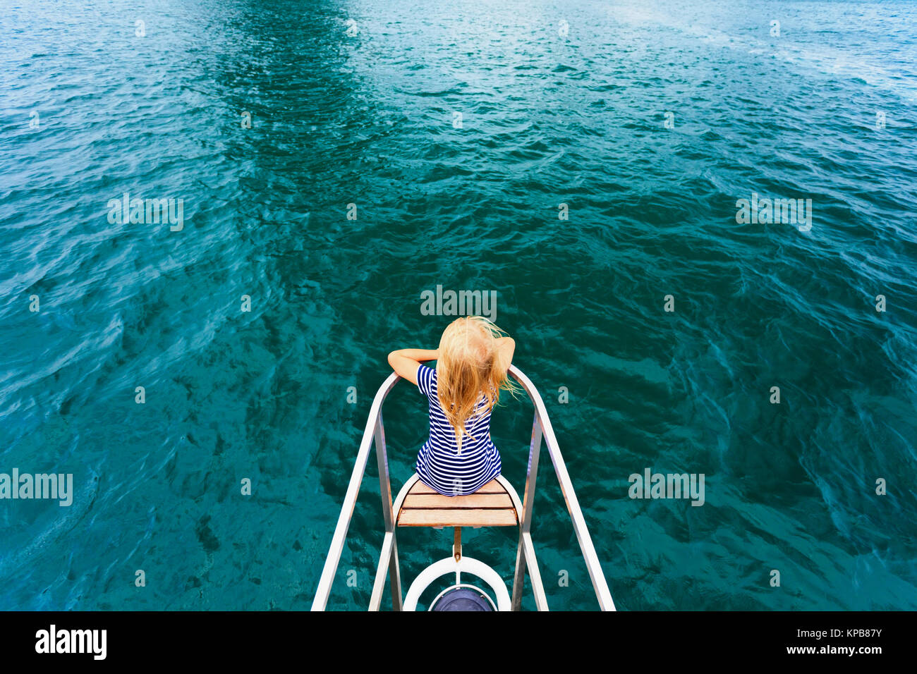 Joyful child portrait. Happy little baby girl on board of sailing yacht have fun discovering islands in tropical - Stock Image