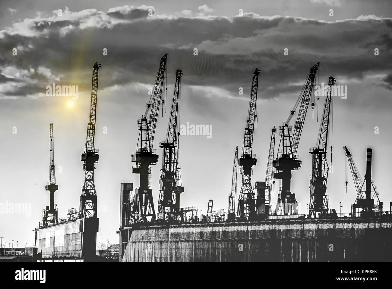 Hamburg Harbor Cranes in Sunset - Stock Image