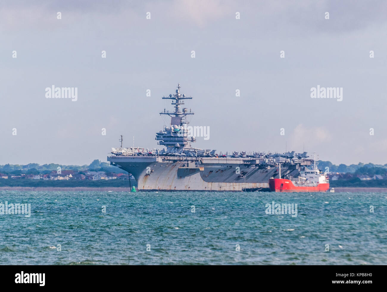 American aircraft carrier, USS George HW Bush visiting Portsmouth, anchored in The Solent at Stokes Bay, near Gosport - Stock Image