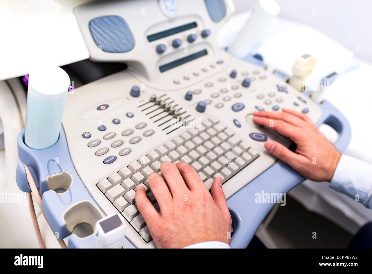 Close up view at doctors hands working on ultrasounds keyboard - Stock Image
