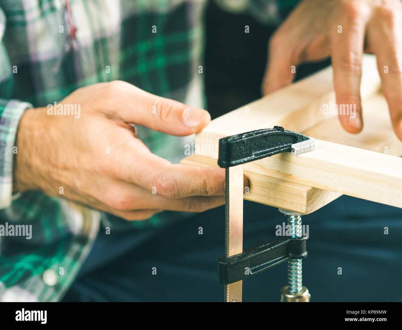 Man crafting wooden chair object keeping wooden boards in hands. Do it yourself project making process. Using press - Stock Image