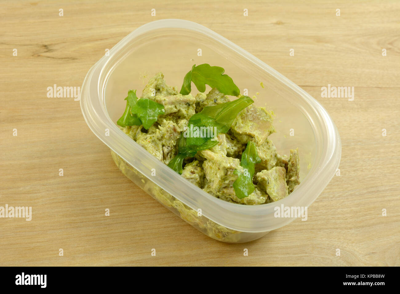 Pesto chicken salad packed in plastic storage container for lunch at