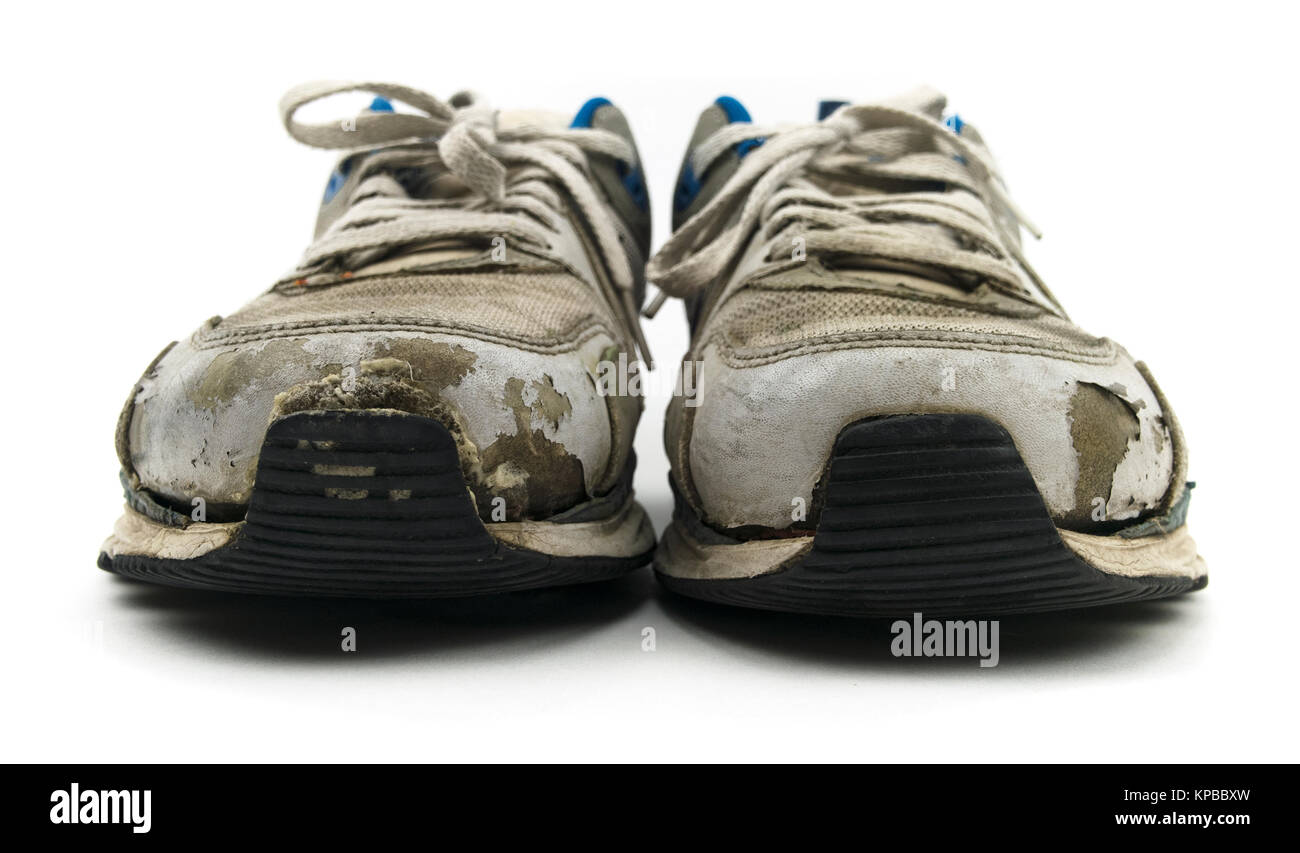 Isolated old sneaker shoes on a white background. - Stock Image