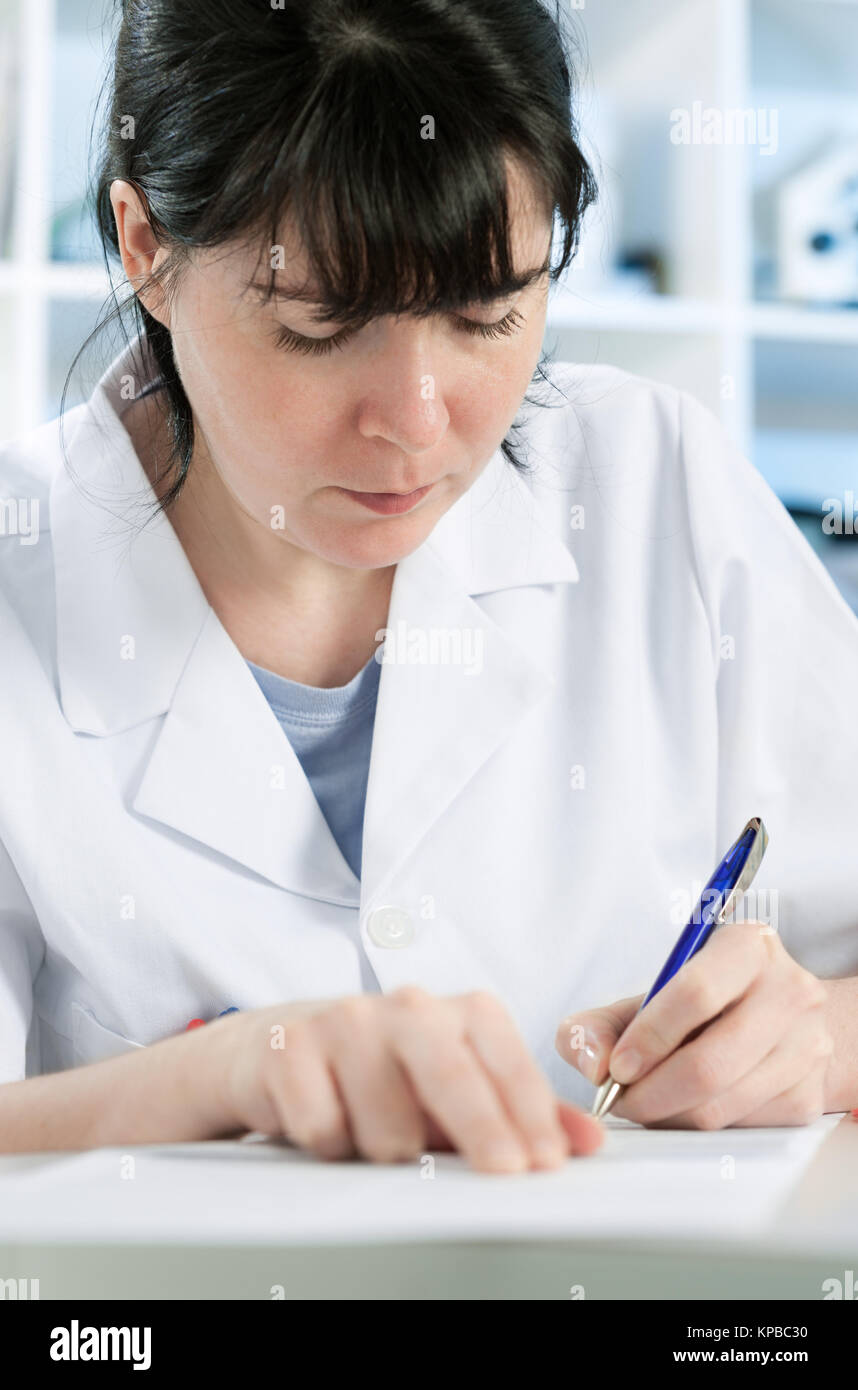 Scientist or a medic in a white coat making notes - Stock Image