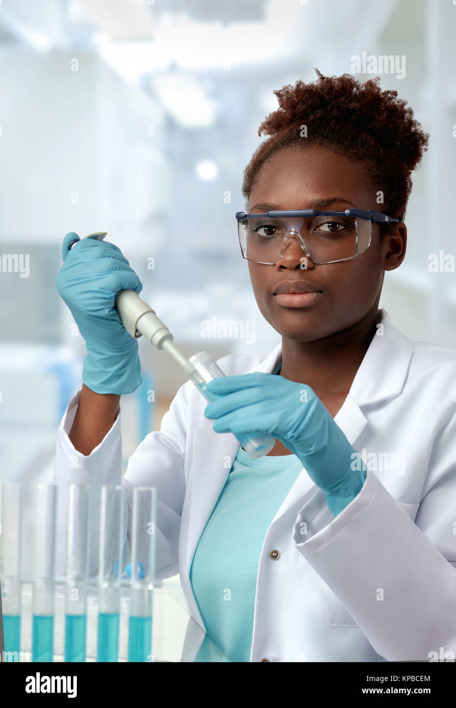 African-american scientist or graduate student in lab coat and protective wear works in modern laboratory - Stock Image