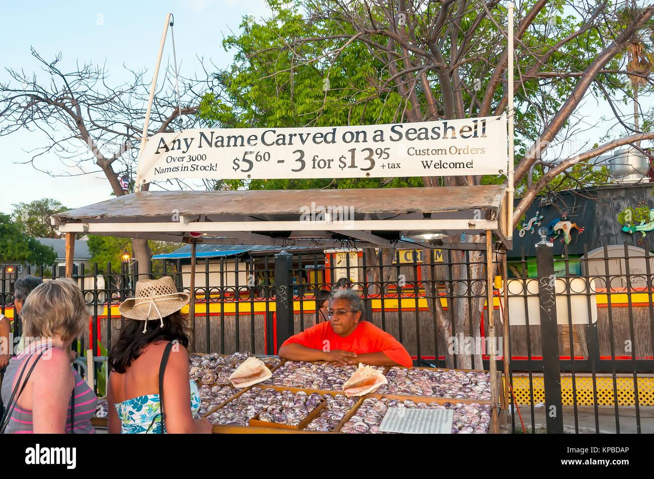 Two women shopping for souvemir at Any Name Carved on a Seashell kisk, Mallory Square Sunset Celebration, Key West, - Stock Image