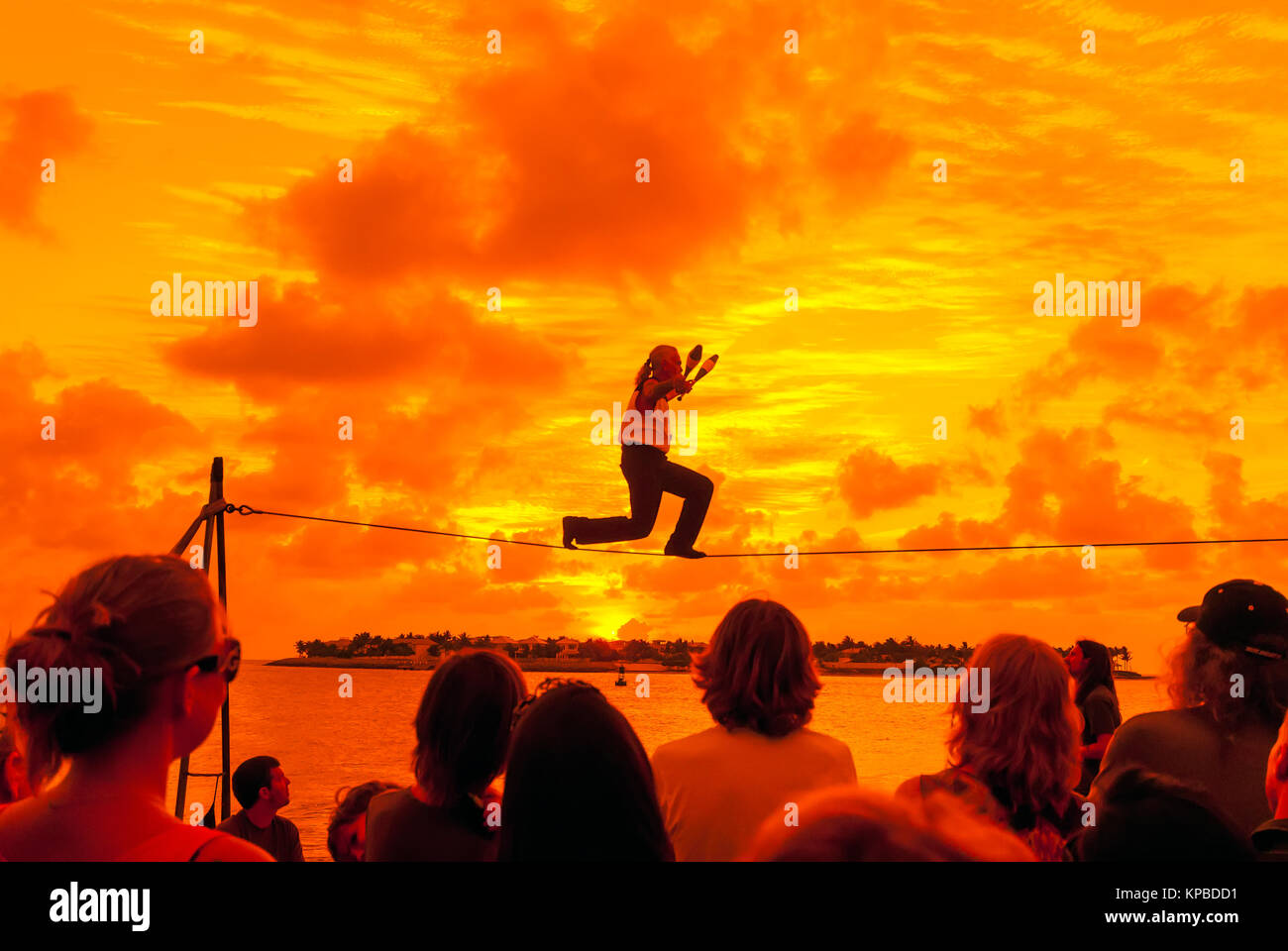 Tight Rope Walker at Key West Sunset Celebration in Mallory Square with bright orange sunset, Florida - Stock Image