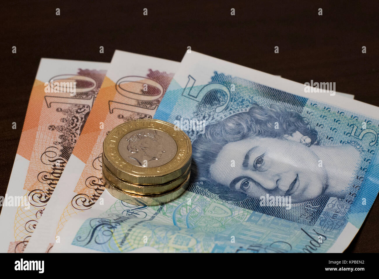 Great British pounds sterling new series G banknotes and coins. GBP 28 composed of two ten-pound notes, one five - Stock Image