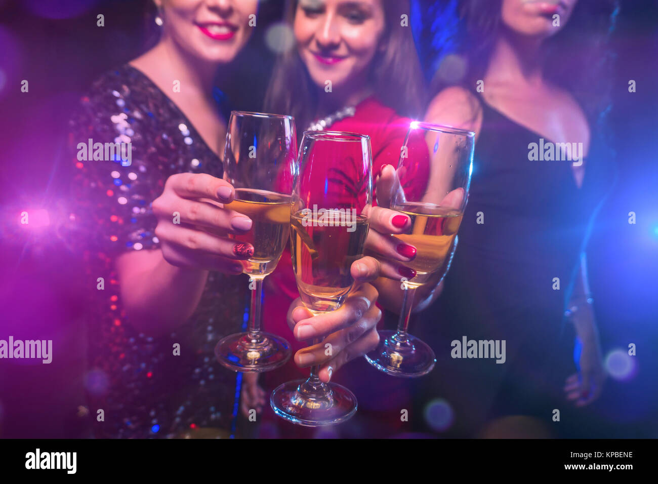 Three women clink glasses with champagne on celebration - Stock Image