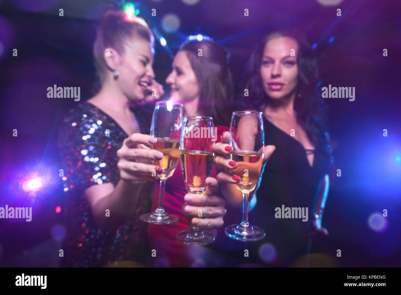 Three women clink glasses with champagne, have fun together on holiday celebration - Stock Image