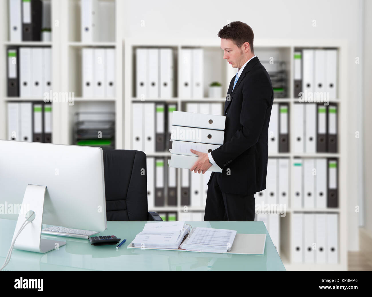 Businessman Carrying Binders By Desk - Stock Image