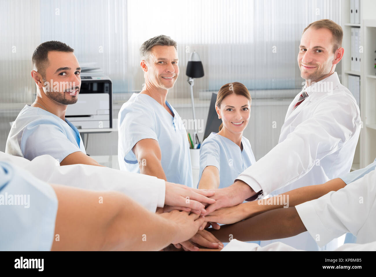 Confident Medical Team Smiling While Joining Hands - Stock Image