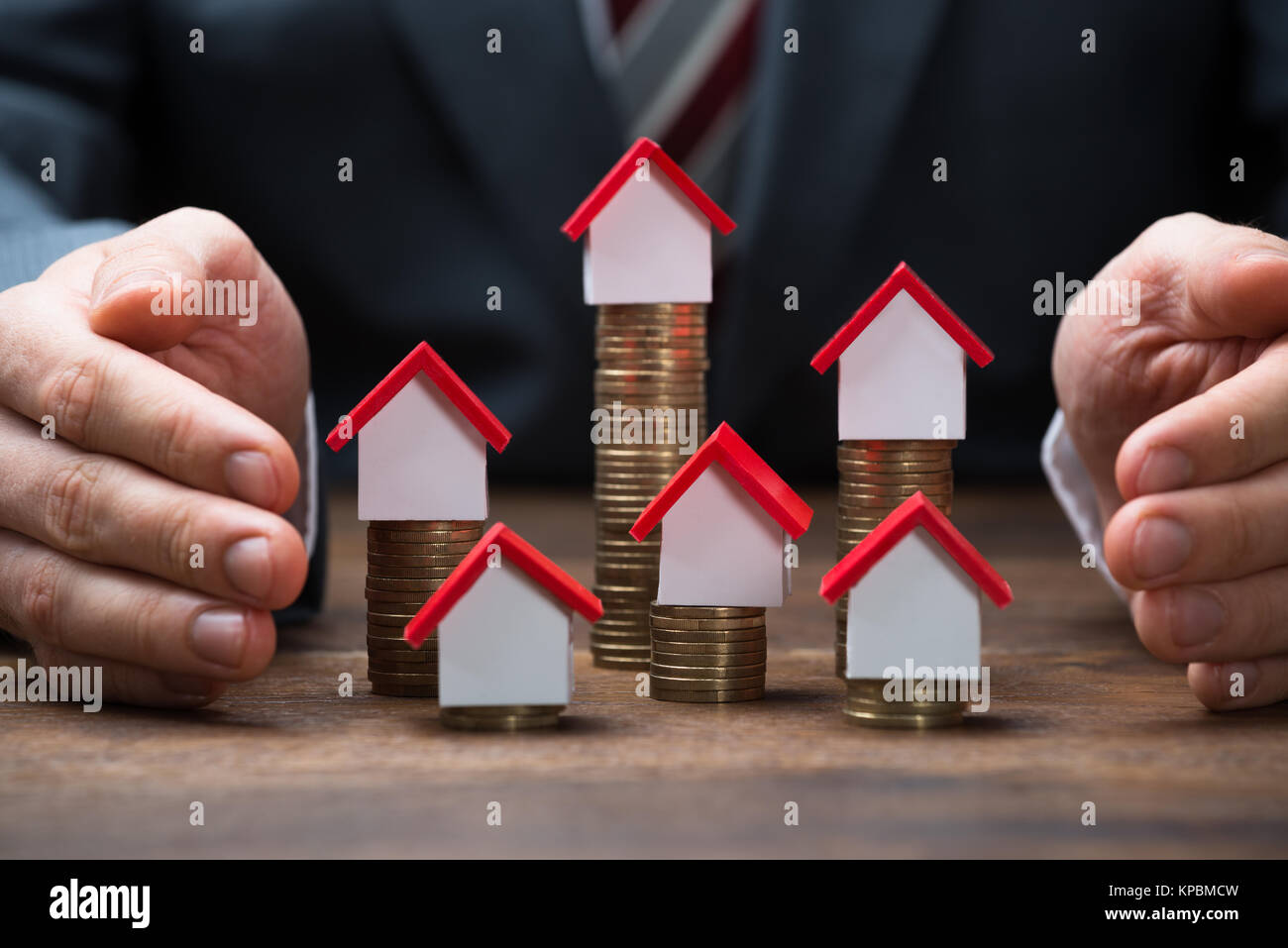 Businessman Covering House Models On Stacked Coins - Stock Image