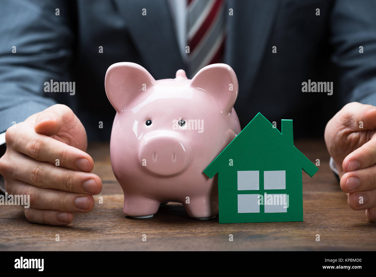Businessman Protecting Green Paper House And Piggybank - Stock Image