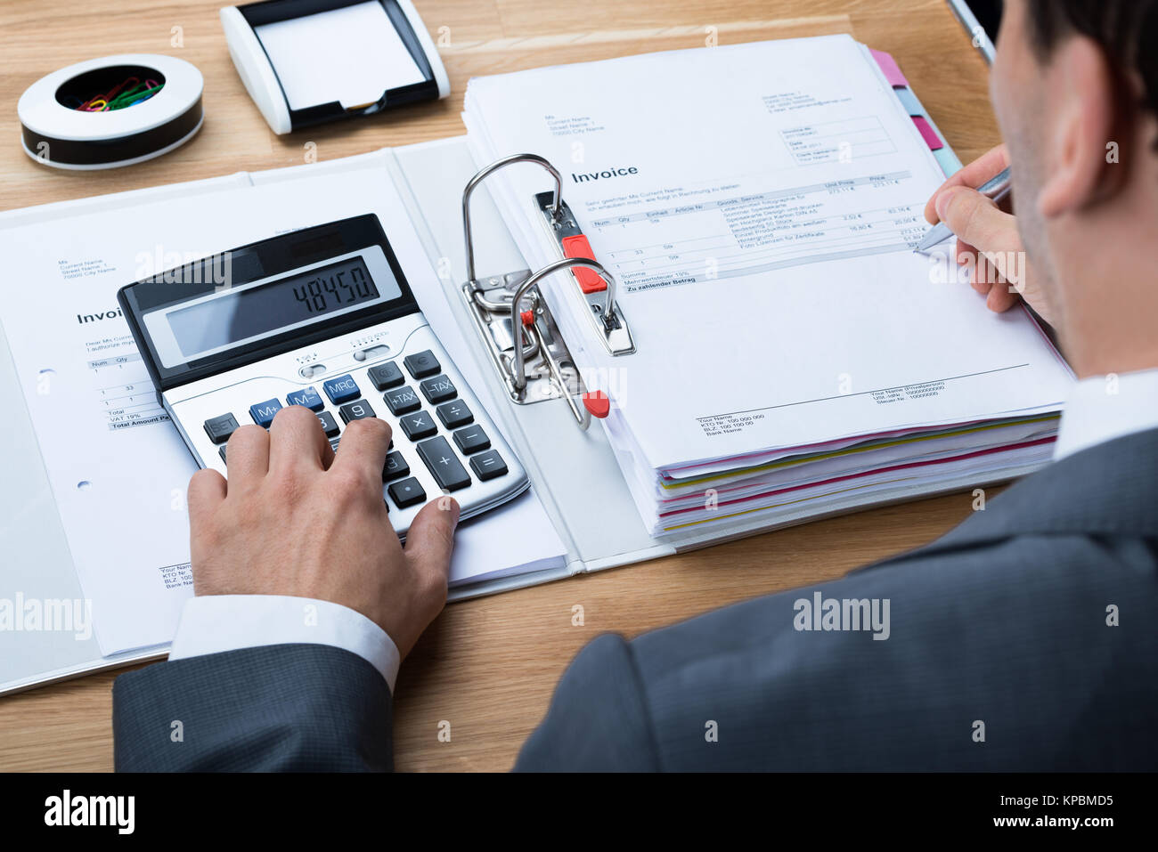 Businessman Calculating Invoice At Office Desk - Stock Image