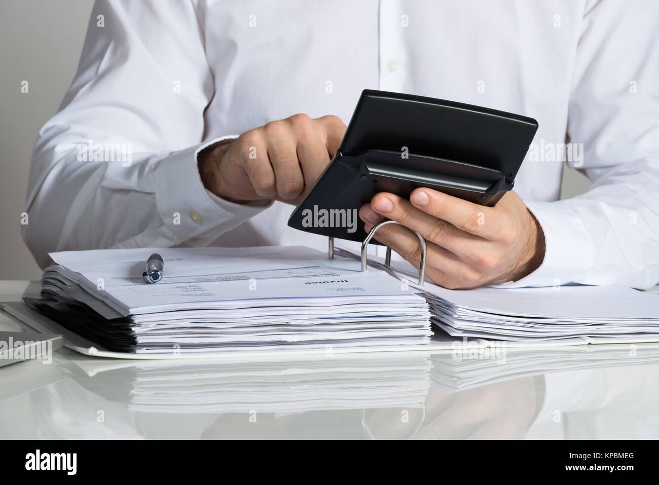 Businessman Calculating Invoice At Desk - Stock Image